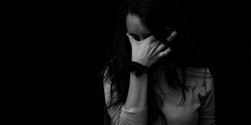 mulher com mão no rosto em ambiente escuro