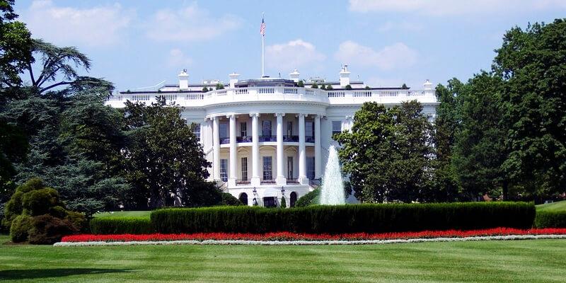 Casa Branca e bandeira dos Estados Unidos vistos de longe