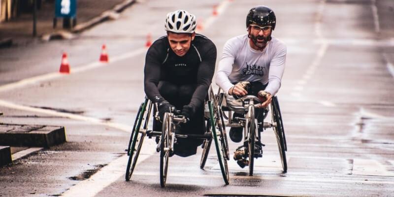dois ciclistas com deficiência participando de corrida
