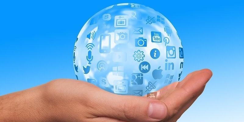 Kugel mit Internetsymbolen in der Hand